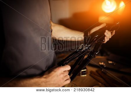 Working process of the leather craft in the workshop. Man holding photographer's belt for camera.Wooden background. Tanner in old tannery.Close up arms.Warm Light for text and design. Web banner size.
