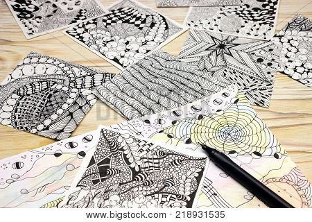 A photo of the abstract doodle patterns made of black liner pen on the wooden table. Pen strokes. Doodle tangle illustration. Zen art sketch illustration. Lesson for artist painters