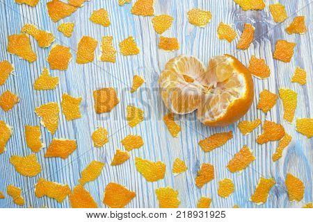 Rustic background. Exotic fruits. An overhead photo of tangerine without peel. Peeled juicy tangerine on the wooden blue table and a lot of pieces of orange peel
