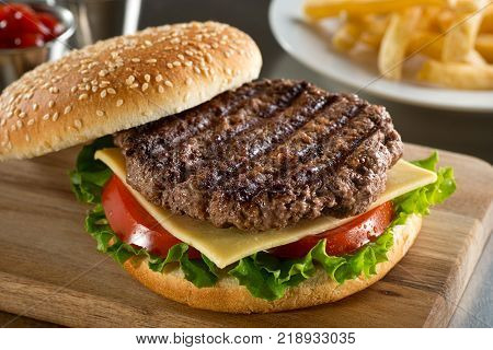 A delicious grilled Angus burger with cheese lettuce and tomato on a sesame seed bun.