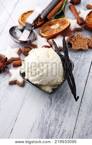 creamy vanilla ice cream on a stylish modern plate on a wooden table with dried vanilla