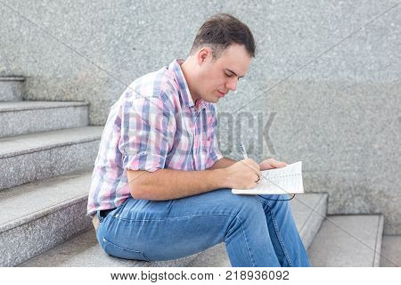 Concentrated student boy making notes in workbook outdoors. Busy young man sitting on stairs writing ideas in diary. Education concept