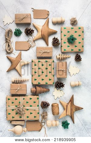 Brown Christsmas present boxes with sparkling embossed fir trees, pine cones, stars, wooden decorations, jute twine, top view, vertical