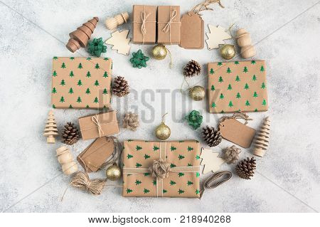 Brown Christsmas present boxes with sparkling embossed fir trees, pine cones, golden baubles, wooden decorations, jute twine arranged in a frame, top view on the light background, copy space