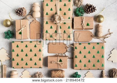 Christmas arrangement, brown present boxes with sparkling embossed fir trees, pine cones, wooden decorations, jute twine, top view