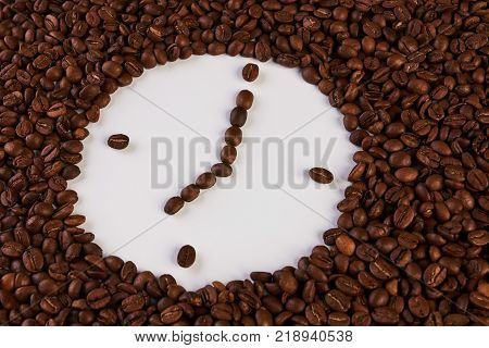 Clock of coffee beans isolated on white background, close-up. Coffee break concept