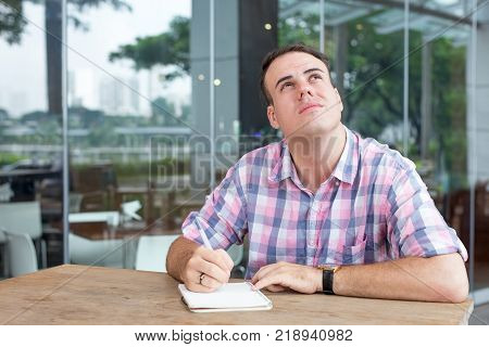 Thoughtful contemplative young man writing business ideas in sidewalk cafe. Pensive calm student finding inspiration. Day dreaming concept
