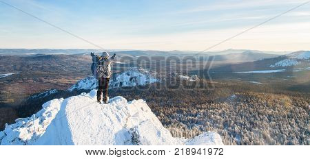 The mountaineer climbed the mountain top, man hiker standing at the peak of rock and celebrates the success with raised hands