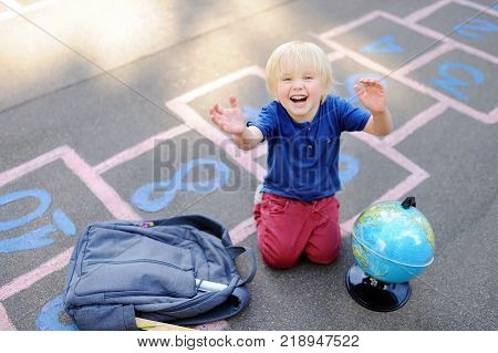 Cute blond boy playing hopscotch game after school with bags laying near. Back to school concept. Little boy on school yard
