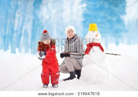 Little boy with his mother/babysitter/grandmother playing snowball fight and building snowman in snowy park. Active outdoors leisure with children in winter. Kid during stroll in a snowy winter park