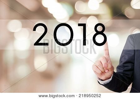 2018 business banner Businessman hand touch 2018 button over blur office background new year business concept