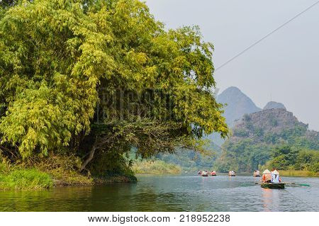 International tourists traveling on local vietnamese small boat along the Ngo Dong river of the Tam Coc, Ninh Binh, Vietnam.