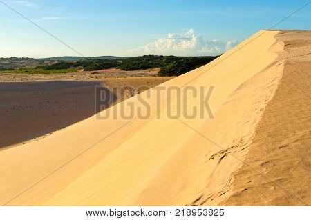 Desert sand dunes and blue sky at sunset