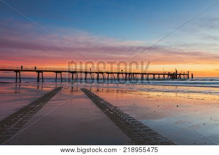 South Australia's Glenelg beach at sunset with tyre tracks in the foreground