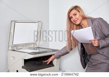 Businesswoman working on a copy machine at the office.