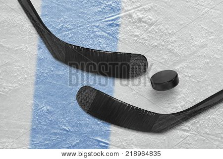 Two sticks a washer a blue line and a hockey field. Concept hockey