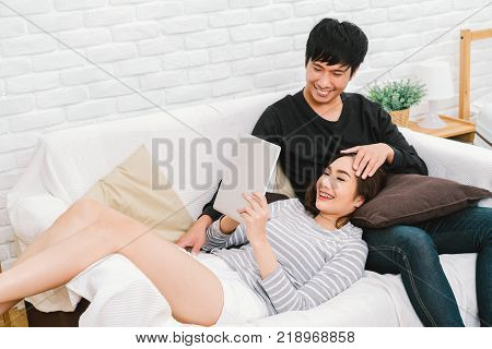 Young Asian lovely couple relax at home sit on sofa using digital tablet together. Girl lay on man lap. Love relationship casual domestic life or modern technology lifestyle concept. With copy space