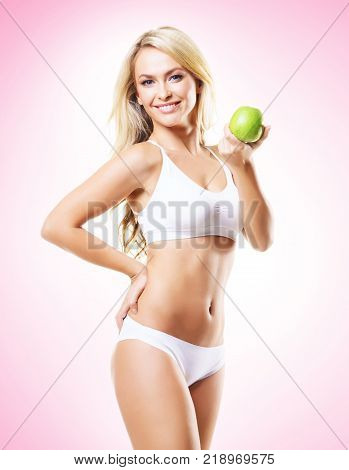 Fit and sporty girl in white underwear. Beautiful and healthy woman eating green apple over magenta background. Sport, fitness, diet, weight loss, nutrition and healthcare concept.