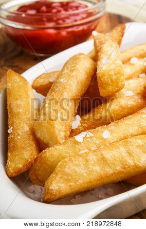 warm french fries with salt and ketchup in a glass bowl