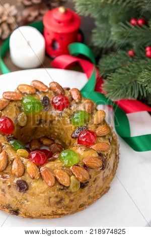 Glazed round hollow colorful Christmas fruitcake topped with almonds and glace cherries on white plate with green pine needles and ribbon decorations
