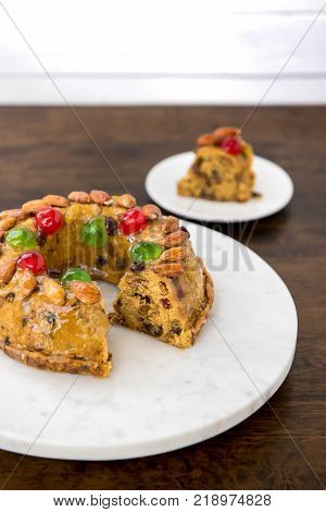Glazed colorful Christmas fruitcake topped with almonds and glace cherries on round white platter