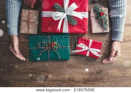 Hands of a girl taking beautiful decorated gift boxes on wood table receives on Christmas holiday - top view with copy space