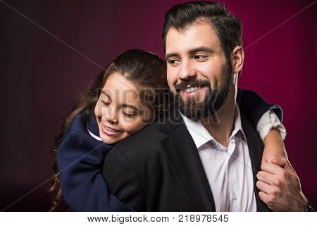 daughter hugging father from back on burgundy