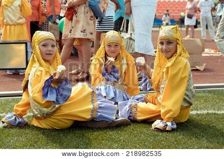 Yoshkar-Ola, Russia - Jule 23, 2016 Three little girls in national Tatar costume at the stadium DRUZHBA during the national Tatar festival
