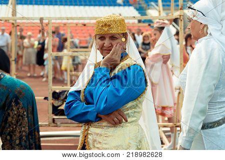 Yoshkar-Ola, Russia - Jule 23, 2016 An adult woman in a Tatar national costume at the DRUZHBA stadium during the Tatar national festival