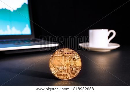 ICO - Initial coin offering concept. On the picture is a laptop with ico rating on the screen a cup of coffee and a coin of electronic currency.