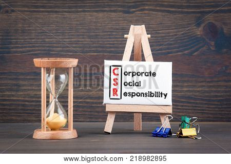 Corporate Social Responsibility. Sandglass, hourglass or egg timer on wooden table showing the last second or last minute or time out