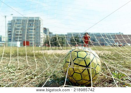 Yoshkar-Ola, Russia - August 20, 2016 A soccer ball in the net of a football goal during a game of street football in one of the streets of the city of Yoshkar-Ola