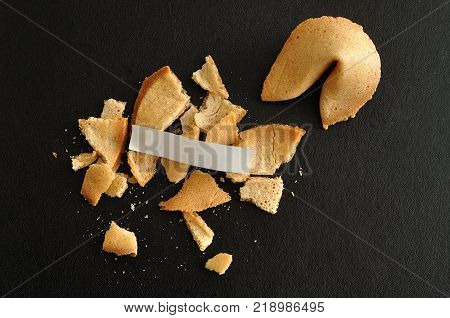 A broken fortune cookie with a piece of paper for a fortune displayed with a whole fortune cookie against a black background