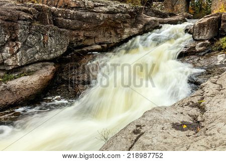 Powerful mountain river close up. Crystal water flows through mossy boulders and rocks. Dark vintage toning filter. Buky Canyon on the Hirs`kyi Tikych river in Ukraine.