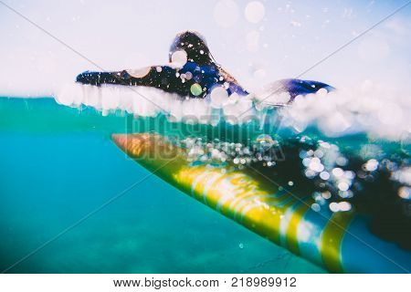 Surf woman on surfboard. Woman with surfboard in ocean during surfing.