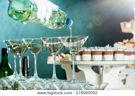 Waiter is pouring martini in polished glasses on the restaurant s catering background with different desserts . A waiter wears perfect white gantlet.
