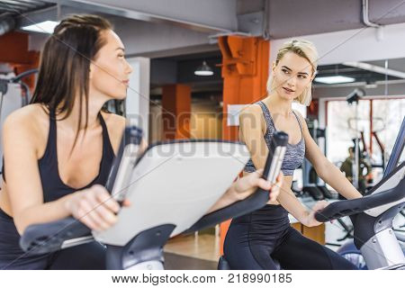 beautiful sportive women working out on elliptical machines at gym