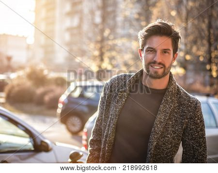 One handsome young man in urban setting in European city, standing in street near cars