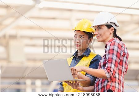 Engineers two woman working on plan building construction with laptop in city
