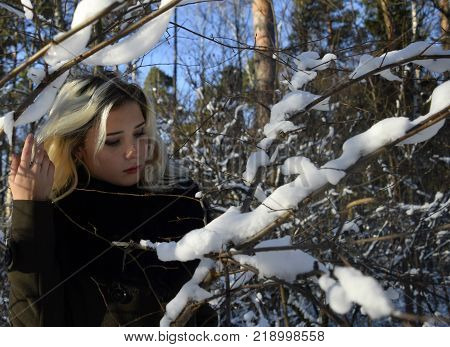 beautiful young blond girl, combing long hair, with downcast eyes stands with uncovered head in the winter brown coat with fur in a snowy forest in cold Sunny clear day