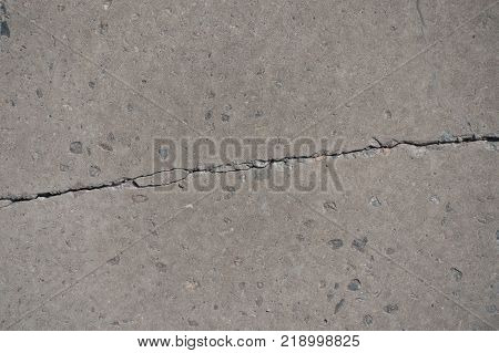 Crack across dry grey flat concrete slab