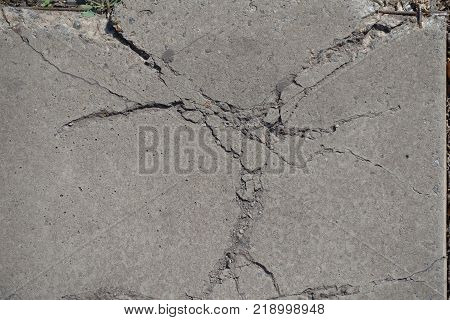 Top view of cracked grey concrete surface