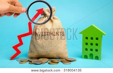 poster of Money bag with the word Investments, up arrow and wooden house. The concept of investing in real estate construction. Effective investment. Buying apartments. Business and finance
