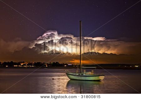 clouds lit by thunderstorm at night over water and town