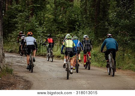 Group Of Cyclists Men And Women Riding On Forest Trail Mountain Bike