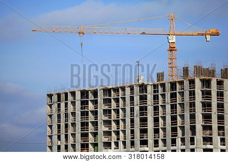 Crane And High-rise Building. Construction Site. The Construction Of Modern Apartment Buildings