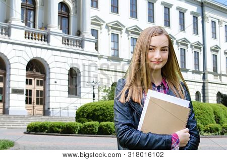 Young Girl High School Or College Student Holding Textbooks, Smiling And Looking At The Camera. She