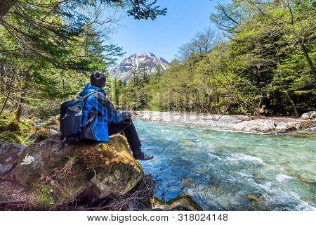 Man Sit Alone On Rock Near Azusa River At Kamikochi In Northern Japan Alps.