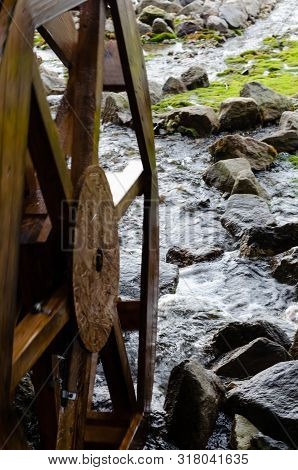 Wooden Grist Mill Water Wheel Turning With The Flow Of Water. Closeup