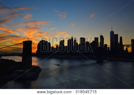 Silhouettes Of Manhattan And Brooklyn Bridge At Sunset Time.